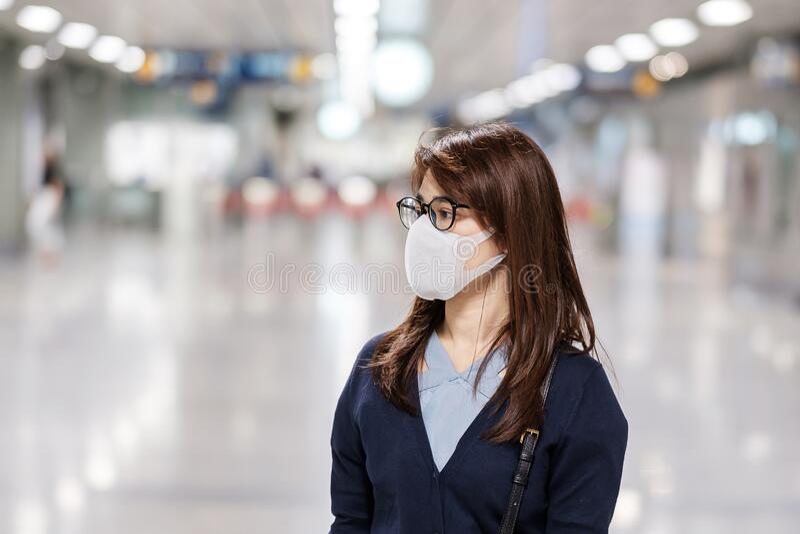A jovem asiática que usa máscara de proteção contra o vírus da febre catarral ou da doença de Corona Covid- 19 no aeroporto é con foto de stock