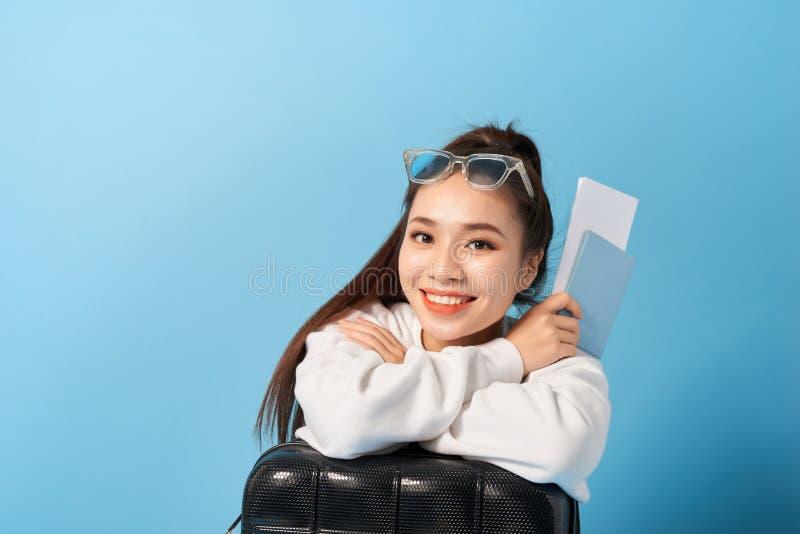 Jovem asiática sentada perto de uma mala, segurando passaporte num fundo azul foto de stock