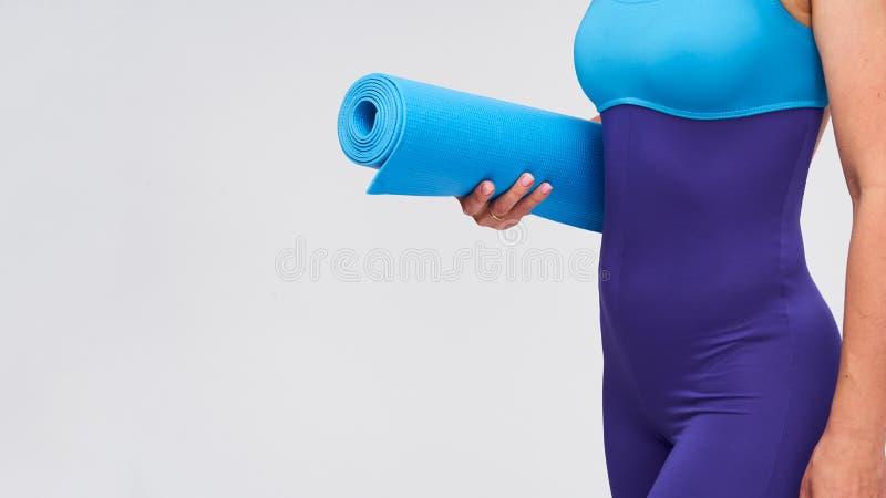 Jovem atlética com tapete para ginástica nas mãos fotografia de stock