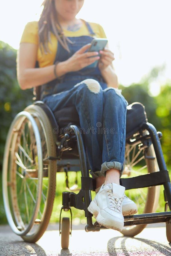 Jovem atraente em cadeira de rodas mandando SMS com seu celular fotografia de stock royalty free