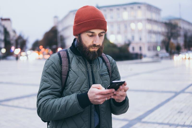 Jovem barbudo olhando na tela do celular enquanto caminhava na rua fotos de stock royalty free