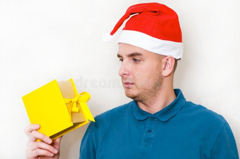 Jovem bonito com surpresa olha para a caixa com um presente cara tem um presente estranho nas mãos emoções negativas foto de stock