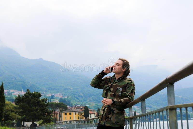 Jovem bonito falando por smartphone perto de banister, lago Como e montanha Alps ao fundo foto de stock