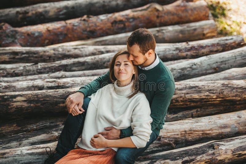 Jovem casal ao ar livre abraçando-se na floresta ao fundo de lenha e tora imagem de stock royalty free
