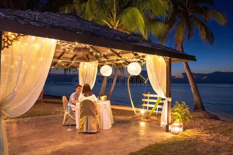 Jovem casal apreciando um jantar romântico na praia tropical fotografia de stock royalty free