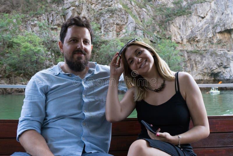 Jovem casal bonito desfrutando de uma excursão em um pequeno barco em um Canyon Garoto com cabelo preto e uma menina caucasiana b foto de stock royalty free