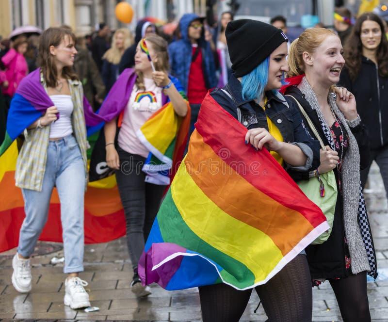 Jovem casal de lésbicas com uma bandeira arco-íris na parada Gay Pride também conhecido como Christopher Street Day CDS em Muniqu foto de stock royalty free