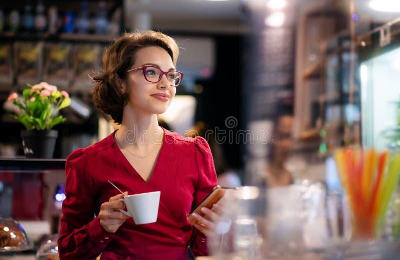 Jovem com café no café, usando smartphone imagem de stock royalty free