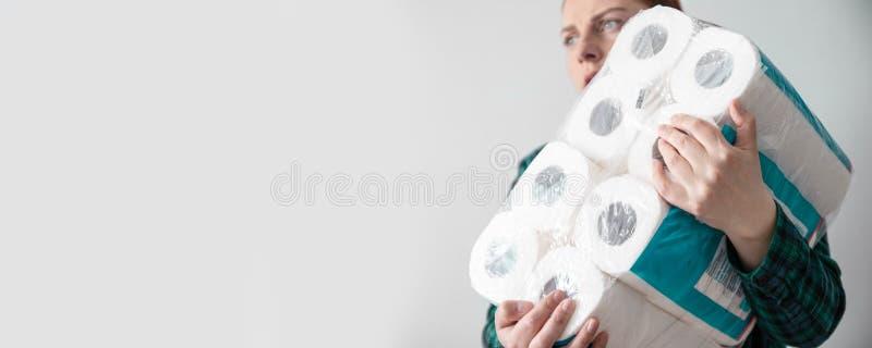 Jovem com papel higiênico embalando Conceito de pânico, perigo de coronavírus Você não pode deixar sua casa para comprar imagens de stock royalty free