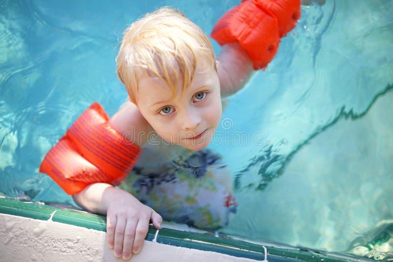 Jovem criança bonito com braço Floaties na piscina fotografia de stock royalty free