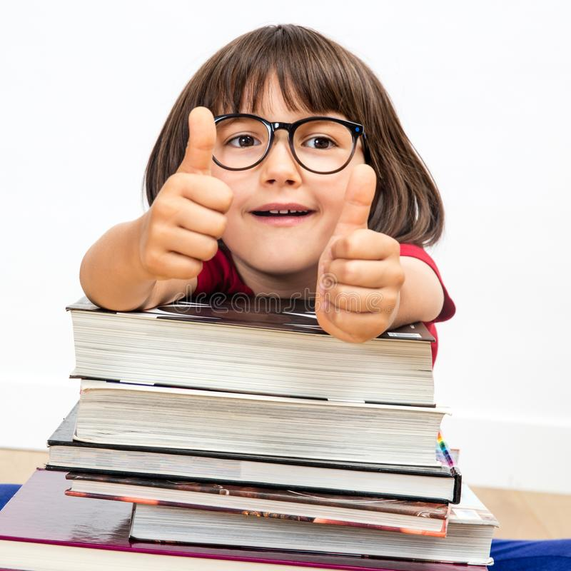 Jovem criança esperta feliz com os polegares que inclinam-se acima nos livros, internos fotografia de stock royalty free