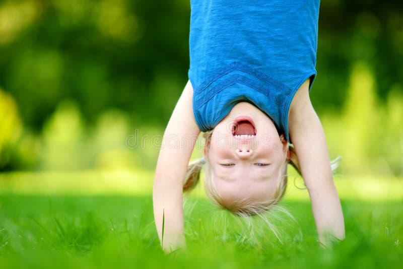 Jovem criança feliz que joga cabeça durante calcanhares na grama verde fotos de stock