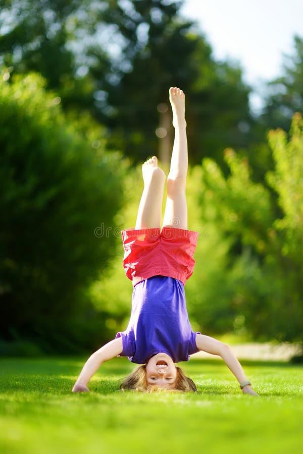 Jovem criança feliz que joga cabeça durante calcanhares na grama verde no parque da mola fotografia de stock royalty free