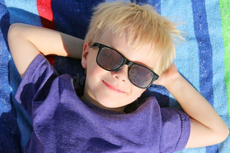 Jovem criança feliz que relaxa na toalha de praia com óculos de sol imagens de stock royalty free