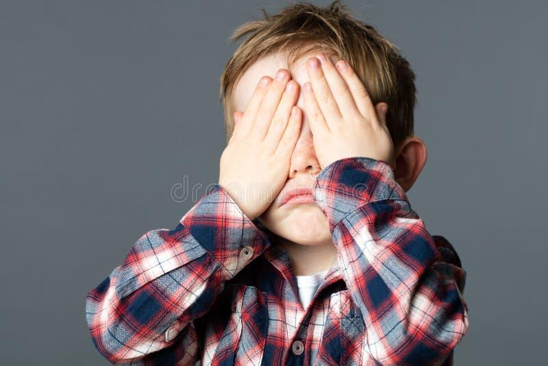 Jovem criança infeliz que cobre seus olhos com as mãos para a tristeza foto de stock royalty free
