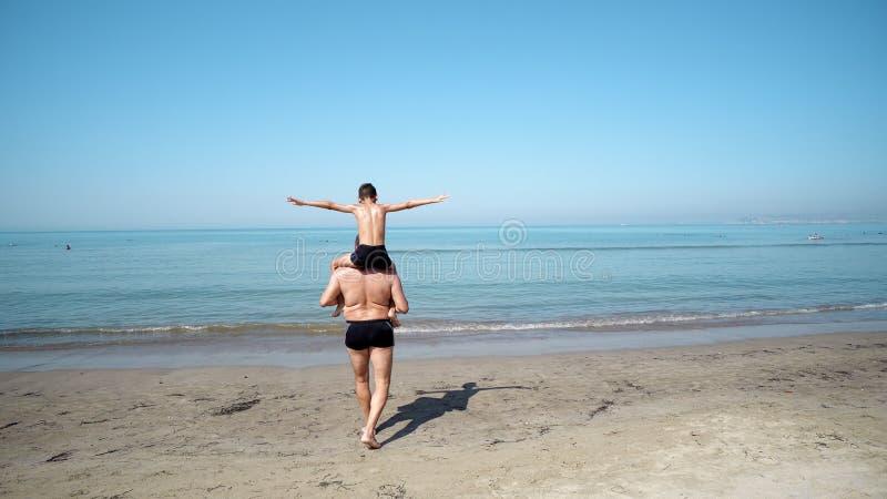 Jovem criança no avião traseiro e no salto do jogo do seu pai na água do mar calma fotografia de stock