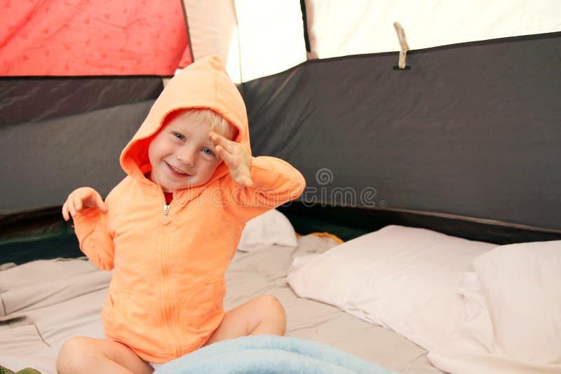 Jovem criança que acorda na barraca após o acampamento imagens de stock