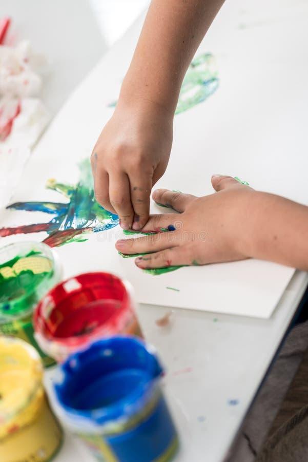 Jovem criança que faz a arte do dedo com pinturas coloridas fotografia de stock