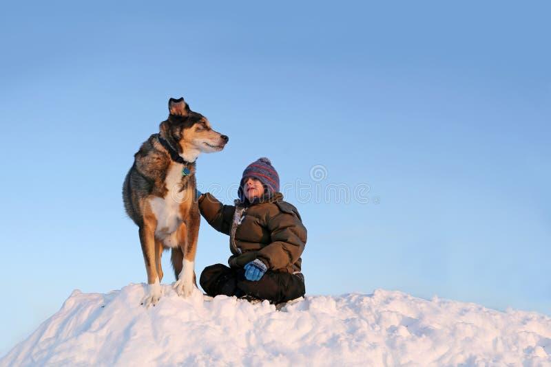 Jovem criança que joga com cão de estimação fora na neve do inverno imagem de stock
