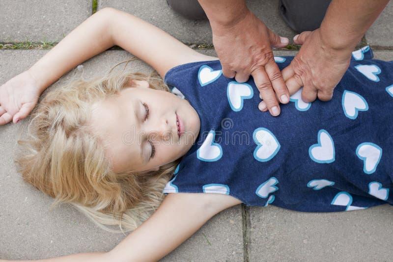 Jovem criança que recebe primeiros socorros imagem de stock