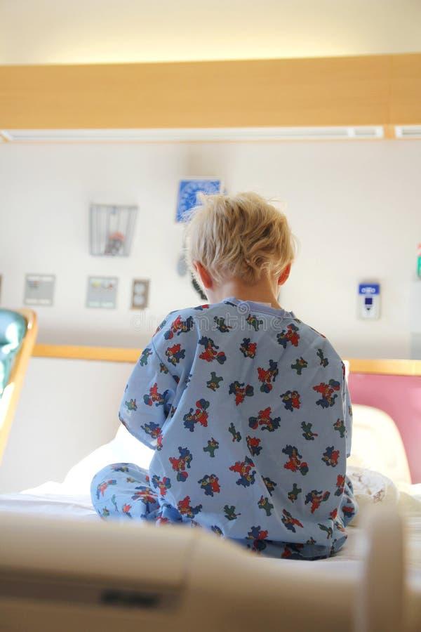 Jovem criança que senta-se na cama de hospital fotografia de stock
