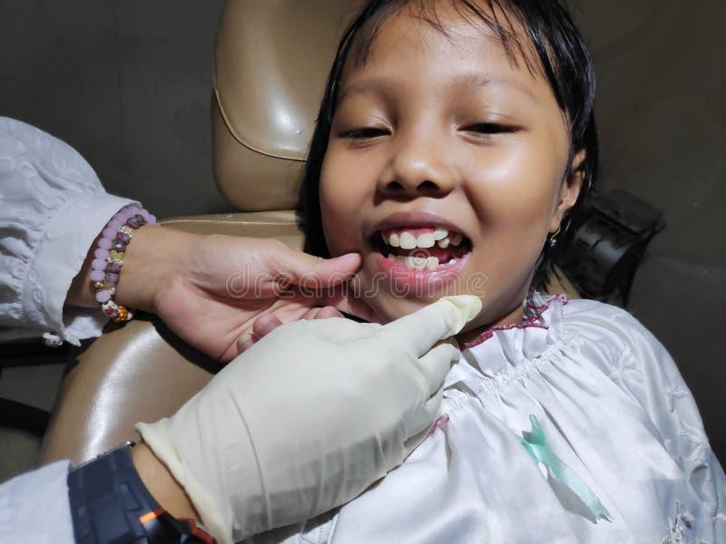 A jovem criança verifica seus dentes do dente fotografia de stock royalty free