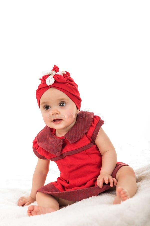 A jovem criança vestiu-se na roupa vermelha que senta-se na cobertura contra o fundo branco foto de stock