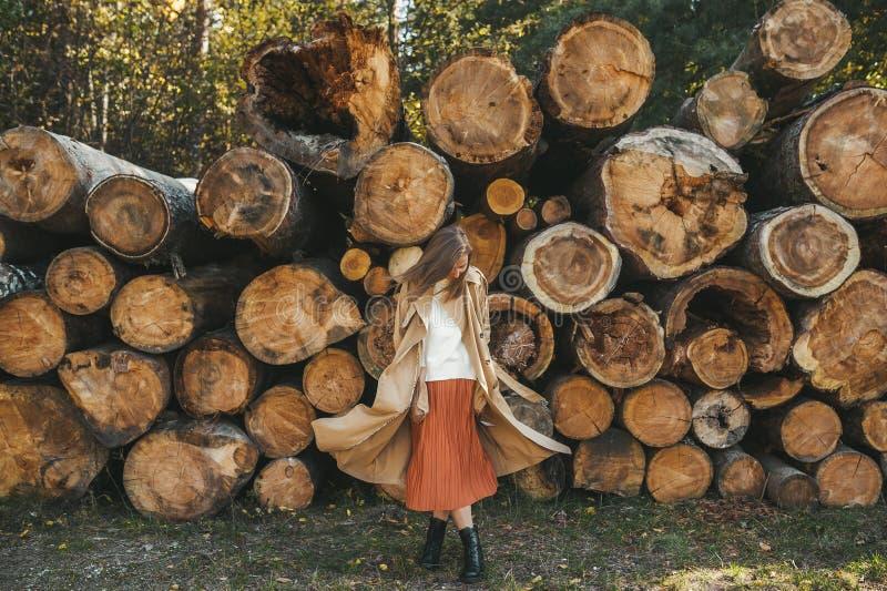 Jovem dançando de casaco bege ao fundo de madeira na natureza Conceito de outono imagens de stock royalty free