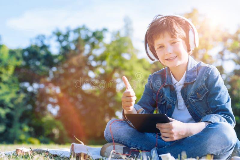 Jovem de irradiação que mostra o sinal super ao apreciar a música imagens de stock royalty free