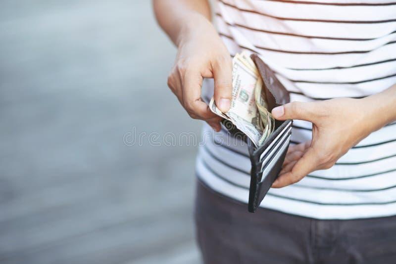 Jovem do estilo de vida que guarda uma carteira nas mãos de um dinheiro da tomada do homem foto de stock royalty free