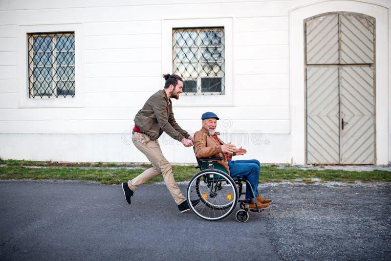 Jovem e seu pai sênior em cadeira de rodas numa caminhada na cidade, se divertindo fotografia de stock