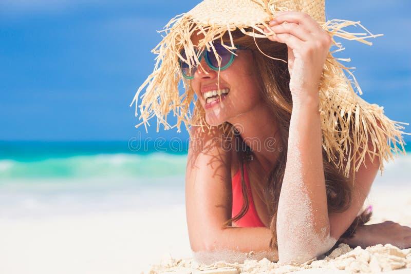 Jovem em biquíni e palha relaxando na praia de caribbean branco imagem de stock