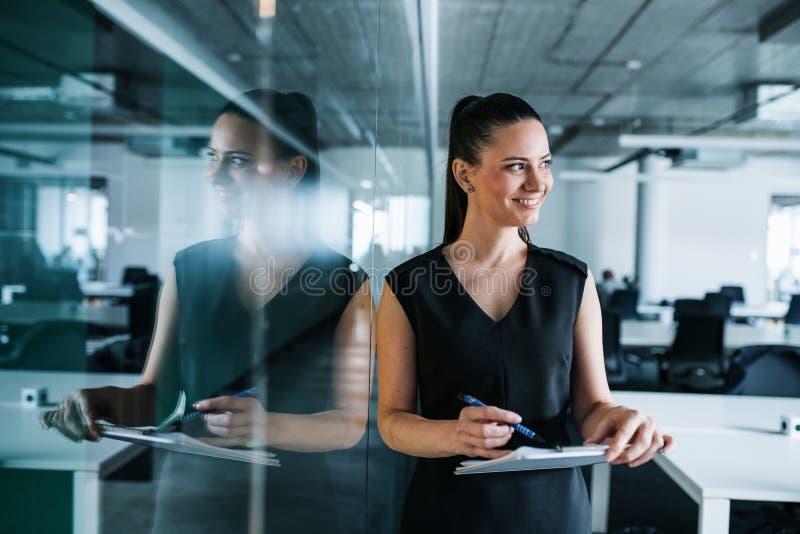 Jovem empresária com prancheta em um escritório, em pé foto de stock royalty free