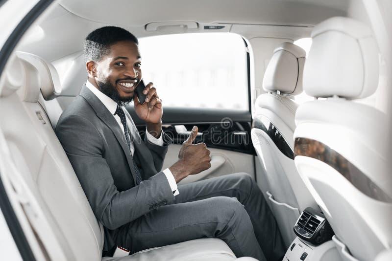 Jovem empresário afro de carro de luxo, mostrando o polegar para cima fotos de stock royalty free