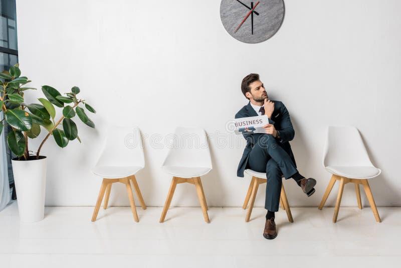 jovem empresário atencioso segurando jornal e esperando fotografia de stock royalty free
