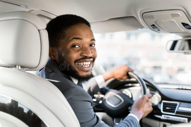 Jovem empresário no banco do motorista sorrindo para a câmera fotografia de stock