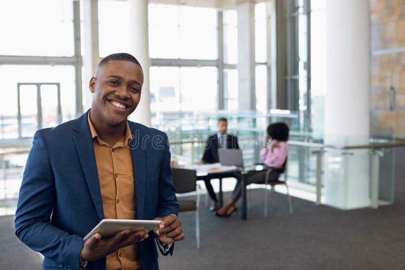 Jovem empresário olhando para uma câmera em um escritório foto de stock royalty free