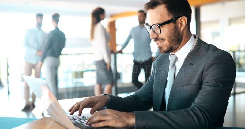 Jovem empresário trabalhando em computador no escritório imagem de stock
