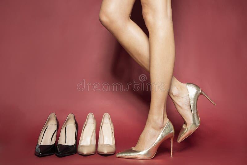 Jovem experimentando sapatos de salto alto enquanto sentado no banco imagem de stock royalty free