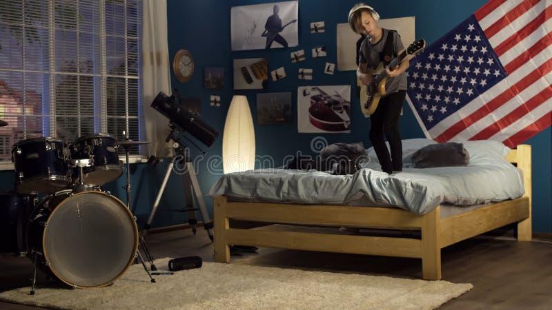 Jovem expressivo que joga a guitarra no quarto fotos de stock royalty free