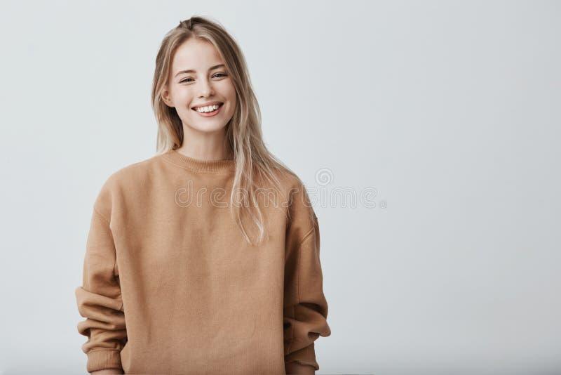 Jovem fêmea positivo alegre com o cabelo louro, vestido ocasionalmente, contente de receber felicitações da graduação de fotografia de stock
