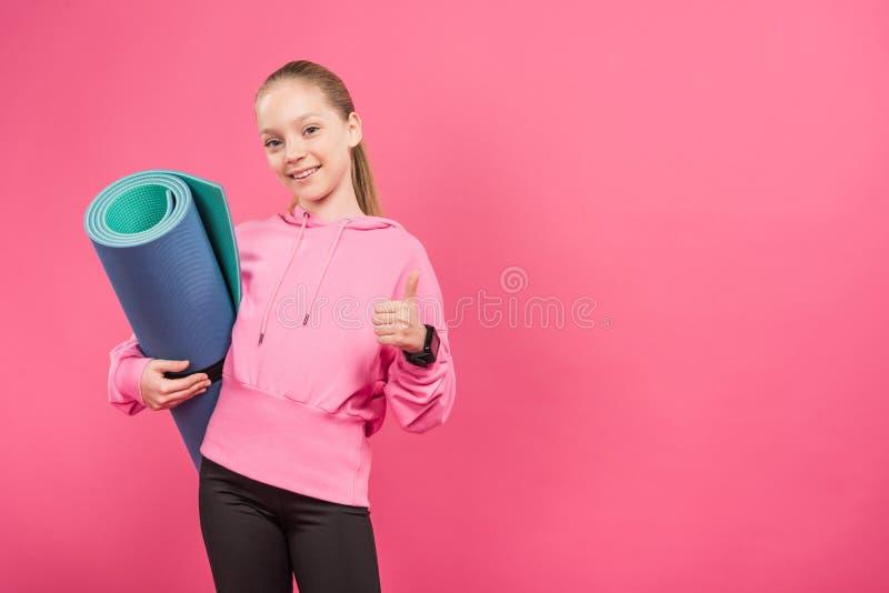 jovem fêmea que guarda a esteira da aptidão e que mostra o polegar acima, isolado foto de stock royalty free