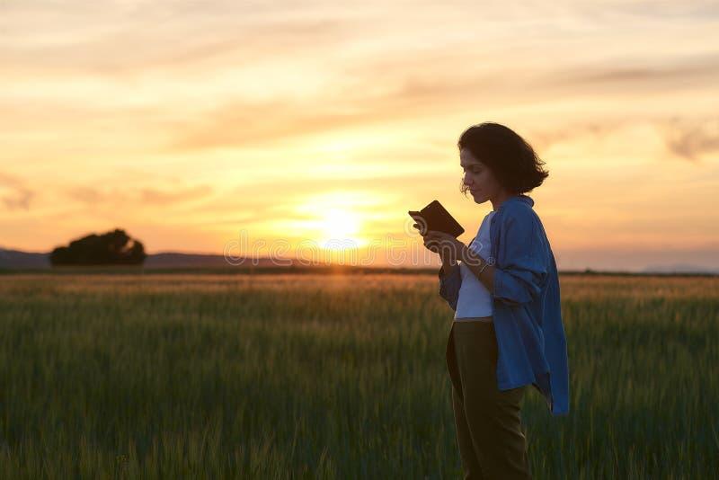 Jovem fala com seu smartphone em um campo fotos de stock