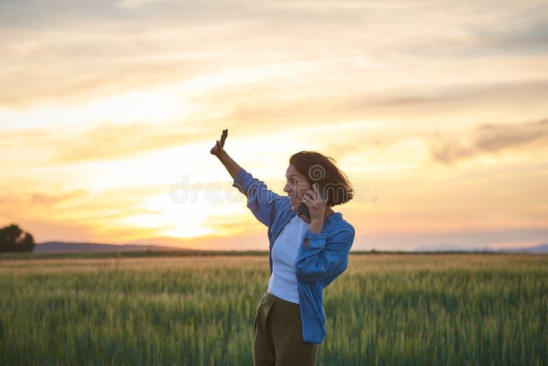 Jovem fala com seu smartphone em um campo fotografia de stock royalty free