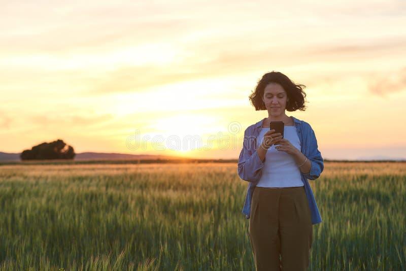 Jovem fala com seu smartphone em um campo foto de stock royalty free
