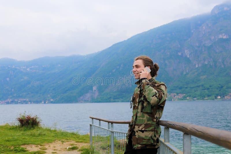 Jovem falando por smartphone perto de banister, lago Como e montanha Alps ao fundo imagens de stock royalty free