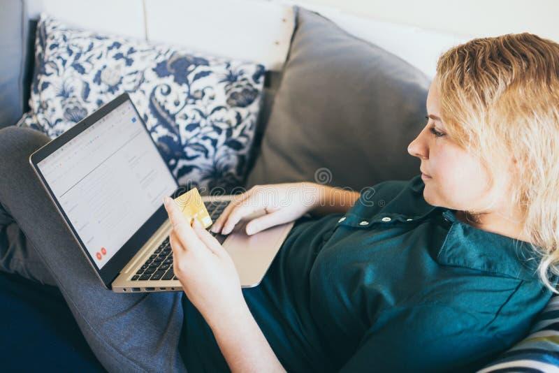 Jovem fazendo compras online com cartão de crédito no sofá, olhando para a tela do laptop e sorrindo imagem de stock