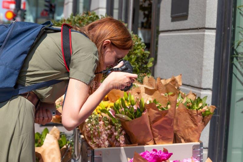 A jovem fotógrafa faz uma foto de um sorteado buquê de flores em uma loja na rua foto de stock