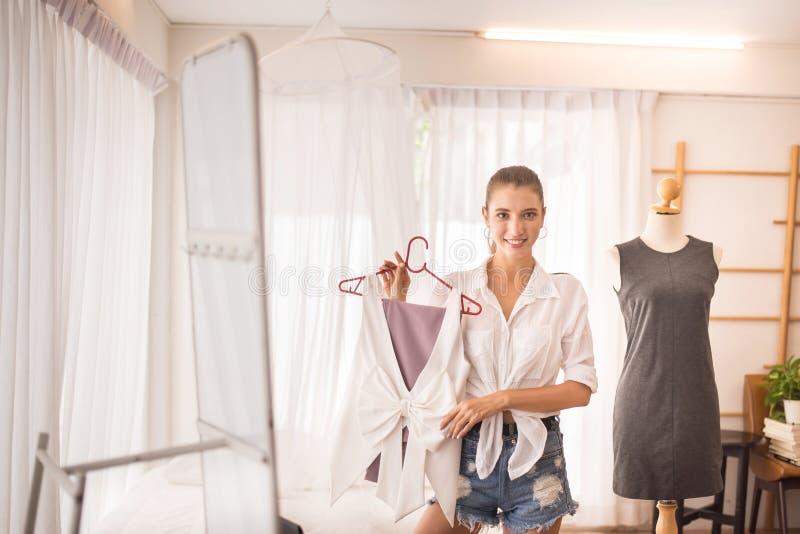 Jovem linda em casa e escolhendo vestidos, feliz e sorridente, conceito de moda e estilo de vida fotos de stock royalty free
