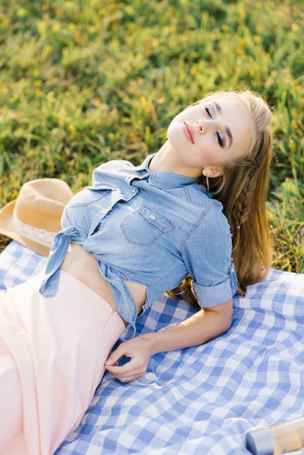 A jovem linda mulher deitada num cobertor de plástico na grama com os olhos fechados, descanso de verão imagem de stock